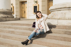 Young beautiful girl sits on the steps of the theater Royalty Free Stock Image