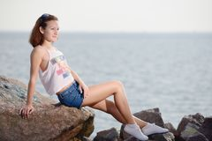 Young beautiful girl sits on stone near sea Royalty Free Stock Photo