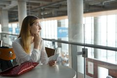 Young beautiful girl sits at table with ticket and waits for airplane Stock Photography