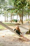 Young beautiful girl sitting barefoot on wicker hammock, sand and trees in background. stock photos