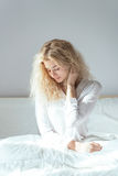 Young beautiful girl sitting on a bed. Young beautiful girl woke up and sitting on a bed Stock Image