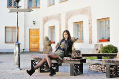 Young beautiful girl sitting on bench in an old town. Beautiful girl sitting on bench in an old town Stock Photography