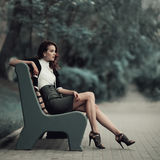 Young beautiful girl sitting on bench Stock Photography