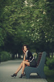 Young beautiful girl sitting on bench Royalty Free Stock Image