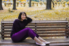 Young beautiful girl sitting on a bench. In the park royalty free stock images