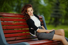 Young beautiful girl sitting on bench in park Royalty Free Stock Image