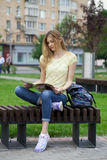 Young beautiful girl sitting on a bench in the summer park Royalty Free Stock Photography
