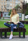 Young beautiful girl sitting on a bench in the summer park Stock Photography