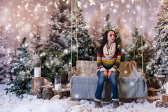 Young beautiful girl sitting on a bench or a swing in a snow-cov Royalty Free Stock Photo