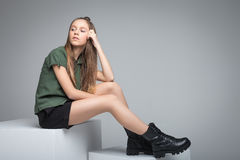 Young beautiful girl sitting on big white cube stock photo