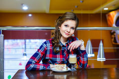 Young beautiful girl sitting in a cafe with a cup of mokachino a Stock Image