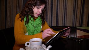 Young beautiful girl sitting in cafe at table and uses a tablet computer. She smiles. Close-up. Brunette in a green. Scarf. The girl takes a cup and drinks tea stock video