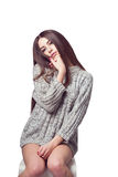 Young beautiful girl sitting on a chair. On a white background. In one gray sweater. Photosession of a sexy brunette. Different emotions. Pending. Hand on the Stock Image