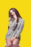 Young beautiful girl sitting on a chair. On a white background. In one gray sweater. Photosession of a sexy brunette. Different emotions. Pending. Hand on the Royalty Free Stock Photos