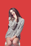 Young beautiful girl sitting on a chair. On a white background. In one gray sweater. Photosession of a sexy brunette. Different emotions. Pending. Hand on the Stock Photos