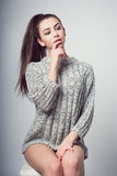 Young beautiful girl sitting on a chair. On a white background. In one gray sweater. Photosession of a sexy brunette. Different emotions. Finger on the lips Stock Photo