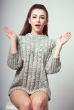 Young beautiful girl sitting on a chair. On a white background. In one gray sweater. Photosession of a sexy brunette. Different emotions. Divorced hands. A sign Stock Photography