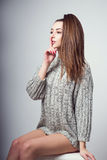 Young beautiful girl sitting on a chair. On a white background. In one gray sweater. Photosession of a sexy brunette. Different emotions. Finger at the lips Royalty Free Stock Photos