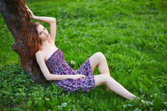 Young beautiful girl sitting on grass Stock Image