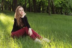 A young beautiful girl sitting on grass. In a park. She has a good make up and long hair Royalty Free Stock Photography
