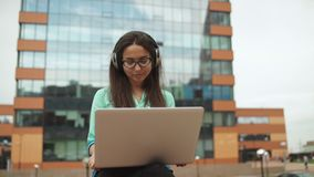 Young beautiful girl sitting with a laptop and headphones stock footage