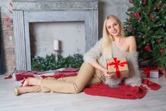 Young beautiful girl sitting near christmas tree Stock Images