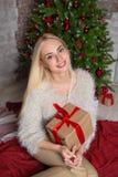 Young beautiful girl sitting near christmas tree Royalty Free Stock Photo