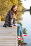 Young beautiful girl sitting on a pier Stock Photo