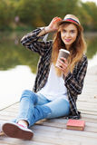 Young beautiful girl sitting on a pier Stock Images