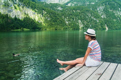 Young beautiful girl sitting on a pier by Konigssee lake with clear green water Stock Photography