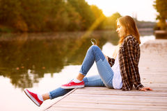 Young beautiful girl sitting on a pier Stock Image