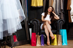 Young beautiful girl sitting in shopping mall with buyings. Young beautiful girl sitting in shopping mall with buyings, smiling stock photos