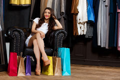 Young beautiful girl sitting in shopping mall with buyings. Young beautiful girl sitting in shopping mall with buyings, smiling royalty free stock image