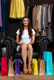 Young beautiful girl sitting in shopping mall with buyings. Young beautiful girl sitting in shopping mall with buyings, smiling, looking at camera royalty free stock photography