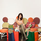 Girl sitting on sofa with shopping bags Royalty Free Stock Images