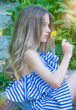 Young beautiful girl sitting on the stairs in the park with flower, Royalty Free Stock Photography