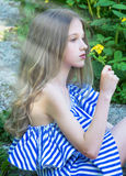 Young beautiful girl sitting on the stairs in the park with flower, Stock Image