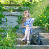Young beautiful girl sitting on the stairs in the park with flower,. Young beauty with long hair Stock Photography