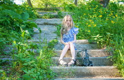 Young beautiful girl sitting on the stairs in the park with flower,. Young beauty with long hair Royalty Free Stock Images