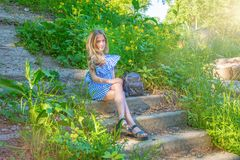 Young beautiful girl sitting on the stairs in the park with flower,. Young beauty with long hair Stock Photo