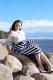 Young beautiful girl sitting on the stone resting shore. Young beautiful girl on a stone on the sea shore Stock Photo