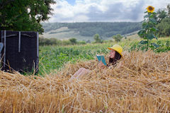 Young beautiful girl sitting on straw and reading a book. Village. Young girl in a straw hat sitting on straw and reading a book. Right growing sunflower. On Stock Photos