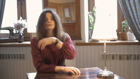 Young beautiful girl sitting at the table, waiting for a friend. stock video footage