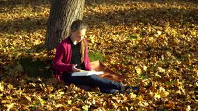 Young beautiful girl sitting under a tree in the autumn forest. A girl is reading a book. She is attentive and stock video footage