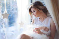 Young beautiful girl sitting on the windowsill, looking out window, morning light, glare royalty free stock image