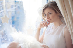 Young beautiful girl sitting on the windowsill, looking out  window,  morning light, glare Stock Image