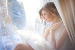 Young beautiful girl sitting on the windowsill, looking out  window,  morning light, glare Stock Photos