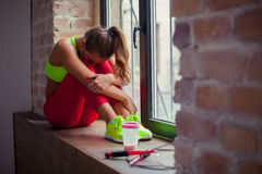 Young beautiful girl is sitting on the windowsill and resting.  Stock Images