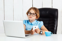 Young beautiful girl sitting at working place in office. Royalty Free Stock Image