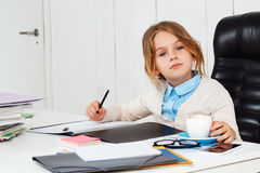 Young beautiful girl sitting at working place in office. Stock Images